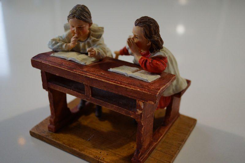 Twee meisjes fluisterend in een schoolbank- foto 2